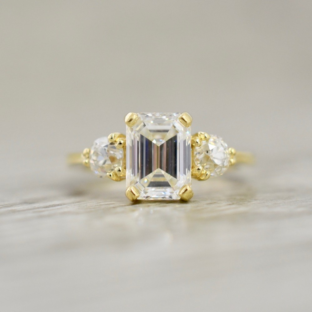 Emerald Cut Diamond Flankedold Europeans In A Basket Set Three Stone  Engagement Ring In Yellow Inside Most Recently Released Prong Set Emerald Cut Diamond Wedding Bands (View 12 of 25)